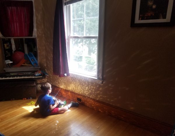 Young boy sitting in front of a window