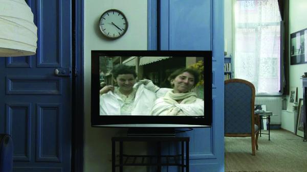 A film still depicting a room with a blue color scheme. The focus is on a video monitor showing  two people dressed in white standing beside one another; they are both smiling.