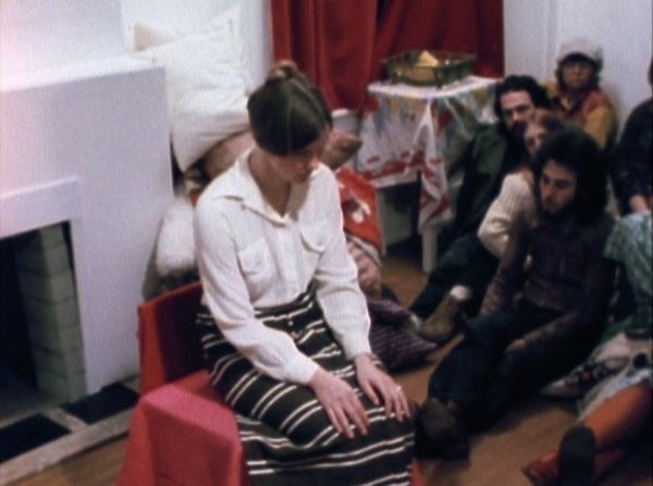 A woman sitting in a chair, looking down, with her hands on her knees. A small audience sits around her on the floor.