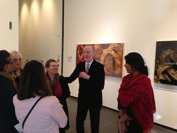 A man in a dark suit speaking to five others in a gallery room; he has his hand on the shoulder of the woman nearest him; they are both smiling.