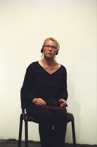 A woman dressed entirely in black, seated in a black chair, with audio equipment in her lap and headphones covering her ears.