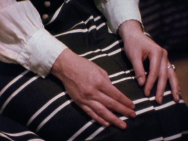 A closeup of a woman's hands on her knees.