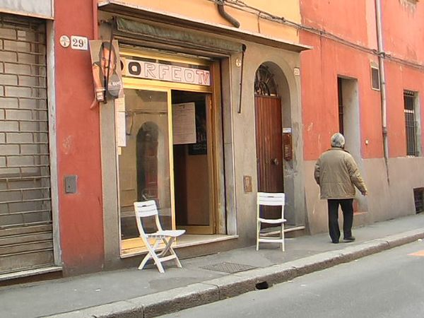 A plain storefront, with an open door and two folding chairs on the sidewalk beside it; the only person depicted, a middle-aged man, is looking away from the doorway.