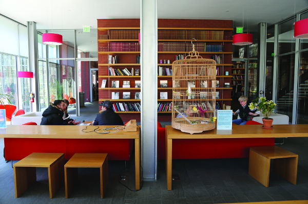 A room in a library with books on shelves, two long wood study tables, and glass walls on either side. A large bird cage sits atop on of the tables, and there are four people visible, seated about the room on small couches.