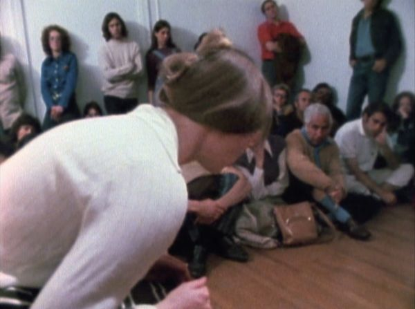 A woman directing her gaze at an empty space on a wood floor. The perspective is from her side, where you can see she is hunched over in front of a small group of people sitting and standing against the room's walls.