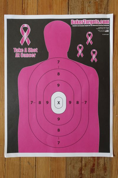 "Firearm target poster, with the human silhouette colored pink beside a caption reading ""Take a Shot at Cancer."""