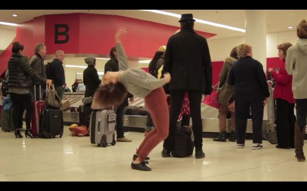 Young woman dancing in an airport beside an airbort baggage claim carousel