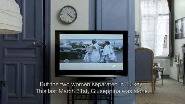 "A film still depicting a television monitor sitting atop stand in a room where blue is the feature color. The subtitle reads ""But the two women separated in Turkey. This last March 31st, Giuseppina was alone."""
