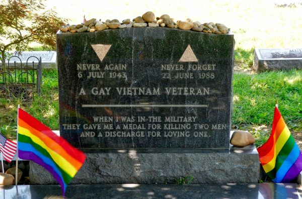A marble gravestone with two rainbow Pride flags beside it.