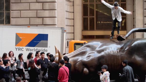 Photograph looking sidelong of a young man dancing atop the bronze Wall Street charging bull statue