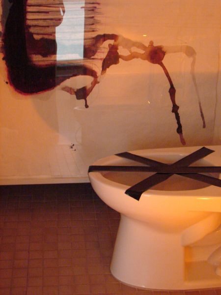 A closeup view of a toilet with tape going across the bowl; in the background a drawing of a hair comb can be seen. The comb looks to be urinating into the bowl.