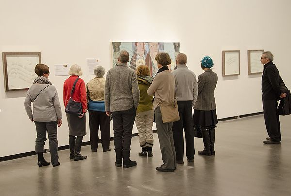Nine people in a gallery looking at works along the same wall.