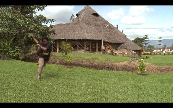 Dancer performing in green space in front of a thatched building