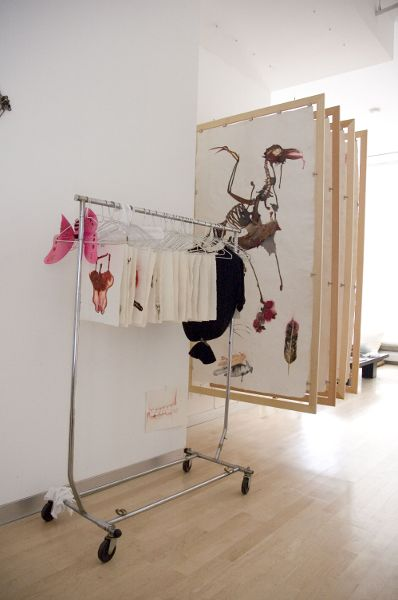A clothing rack with art prints on hangars; in the background there are canvases attached to thin wooden frames with clips, hanging as if they were rugs on display.