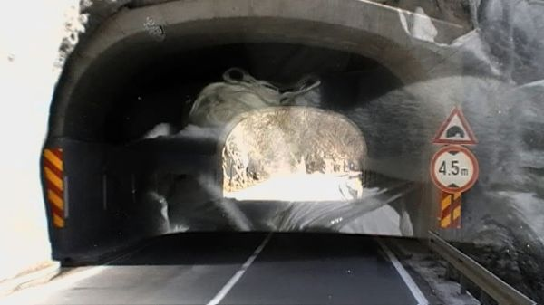 An image of a short tunnel taken from inside a car heading toward it.