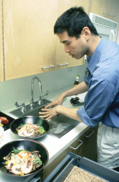 A man in a galley kitchen preparing vegetables in woks aside a sink.