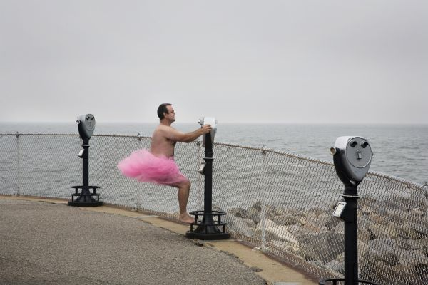 A man, dressed only in a pink tutu, standing on the foot of a coin-operated bincoulars looking out over a large body of water.