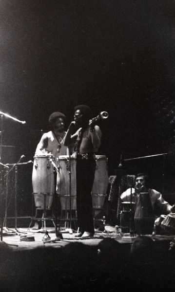 Black-and-white photo of three men standing on stage