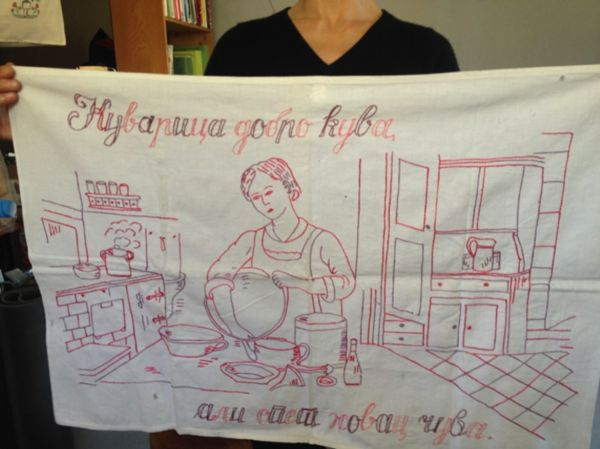 An embroidered kitchen towel, depicting a woman in cooking smock making a meal in the kitchen.