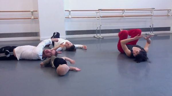 Three dancers posing on the ground with an infant mimicing their movements