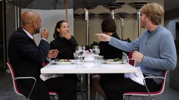 Four people sitting at an outdoor table: two men in the foreground, two woman in the background. The man on the left has his hand in front of his mouth. The man on the right is pointing to the woman on the left, who is smiling and covering her mouth. The other woman is looking back, away from the camera.