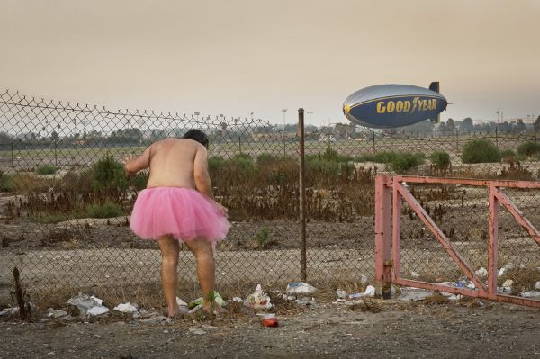 A man, who is dressed only in a pink tutu, stands in dirt and trash beside a chain-link fence. He is looking toward his feet. In the distance a grounded Goodyear blimp is visible.