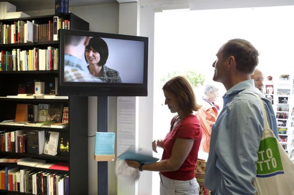 A man and woman, standing in a room adjacent to a gift shop, watching a video monitor mounted to a bookshelf.