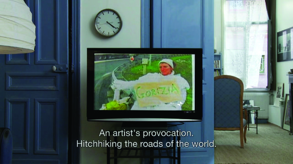 "A film still depicting a room with a blue color scheme. The focus is on a video monitor showing a woman dressed in white beside a road with a sign reading ""Gorizia""; the caption reads ""An artist's provocation. Hitchhiking the roads of the world."""