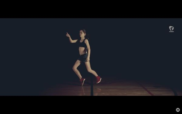 Young woman dancing on a darkened basketball court