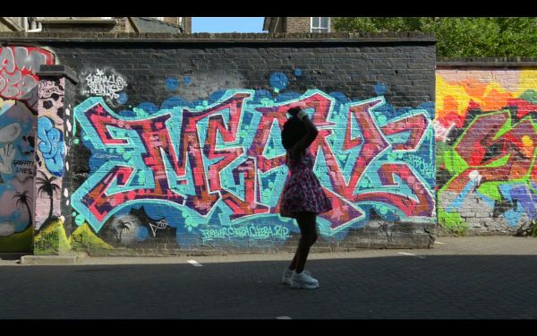 Dancer performing in a parking lot beside a brick wall with covered with graffiti
