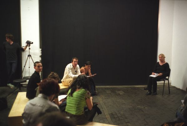 A woman sits in a studio room apart from a small audience. She looks to be engaging with a question. A filmographer stands in the background with a camera on a tripod.