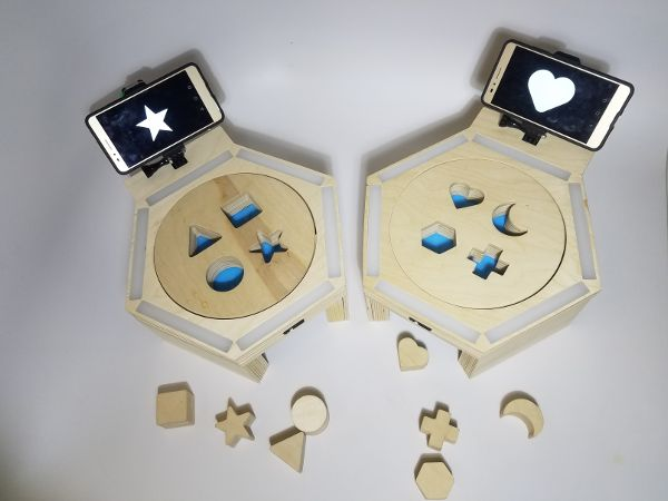 Wooden shapes (square, star, circle, triangle) in front of a platform where there are cutouts for them to fit; a smartphone depicting one of the shapes is attached to the platform