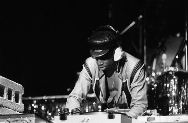 Grandmaster Flash onstage working a turntable with headphones on.