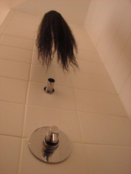 A view within a shower stall, looking from the floor toward the spigot, which is raining hair from a wig instead of water down.