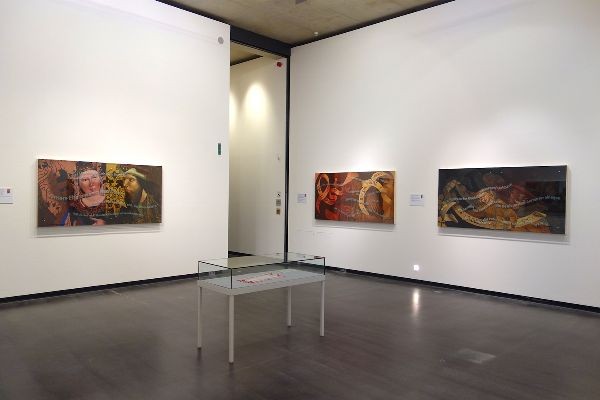 A gallery room empty of people with three pieces shown on the walls and one is a display in the center of the room.