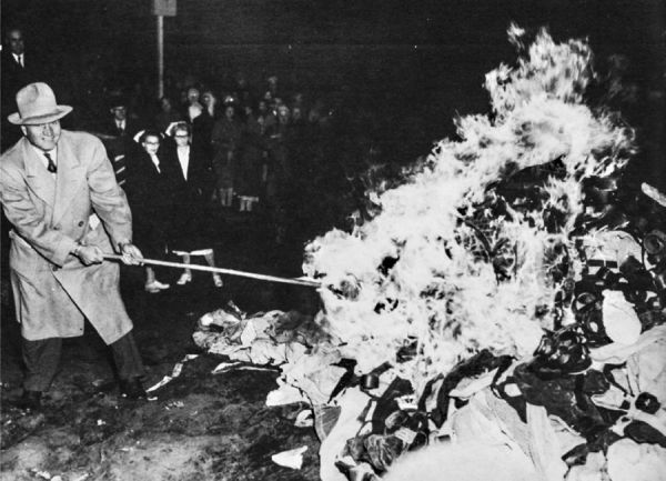 A man dressed in a trench coat and Stetson hat stoking a bonfire with a small crowd of nurses and lookers on in the background.